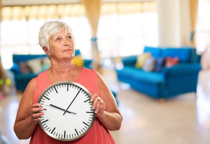 senior woman holding a clock ...