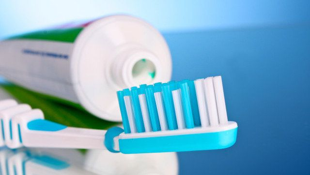 toothpaste and brush on a blue background