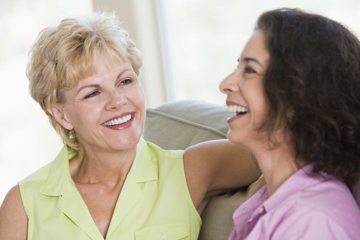 Two women in living room talking and smiling