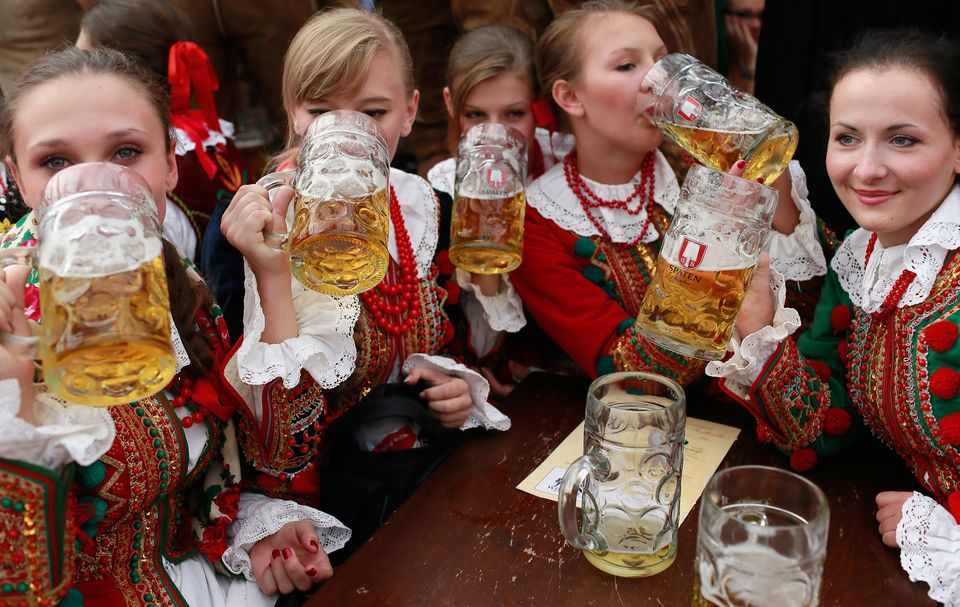 Polish girls, dressed with traditional Polish costume enjoy drinking beer after participating in the opening parade.