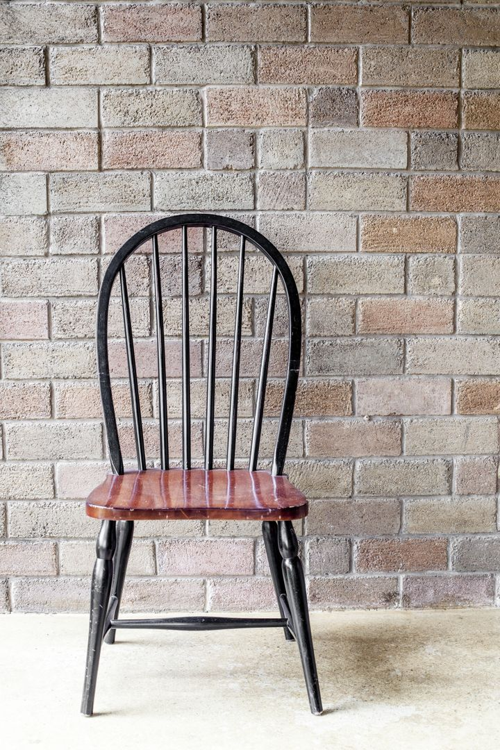 black chair in front of a brick ...