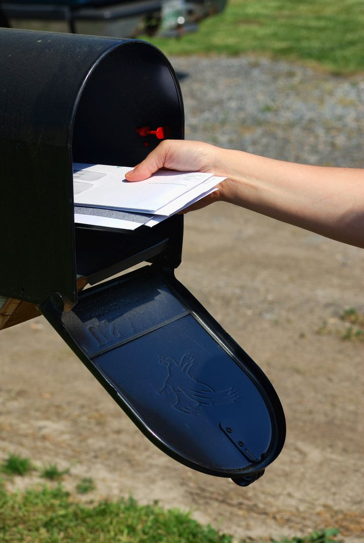 A Person retrieving mail out of a mail box