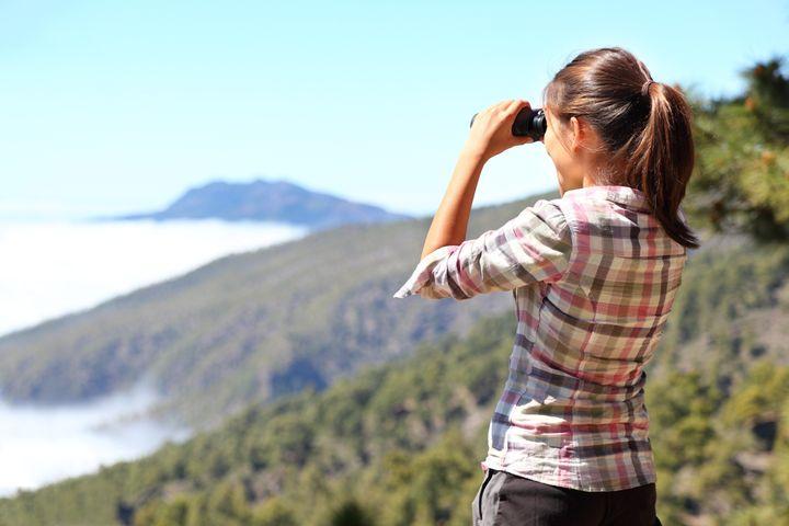 hiker looking in binoculars...