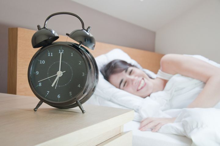 young woman with alarmclock on...