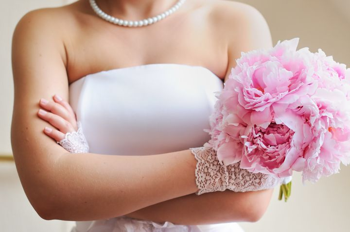 Discontented bride - young woman holding beautiful wedding flowers bouquet (peony)
