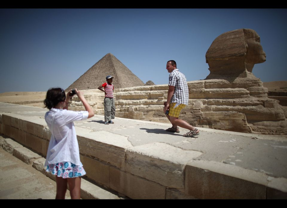 A local boy watches as tourists photograph themselves at the Sphinx and the great Pyramid of Cheops on May 28, 2011 in Giza,