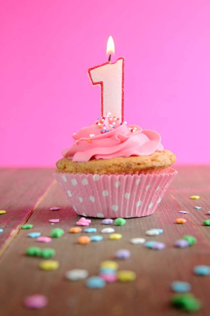 Number one birthday candle on a pink cupcake on a wooden table