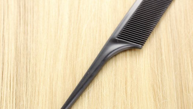 Shiny blond hair with hair comb close-up
