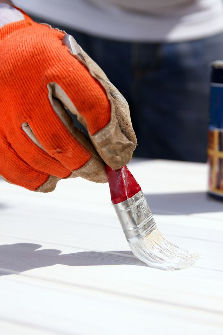 Painting wooden boards with white protective paint with a brush. Do it yourself, DIY