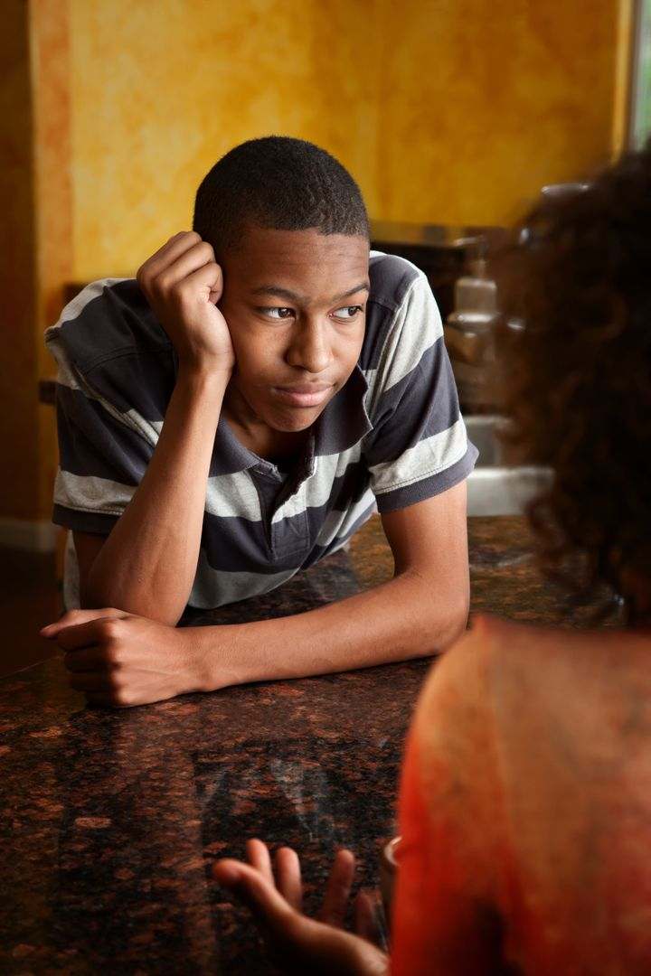 Upset African-American young man and woman talking in kitchen