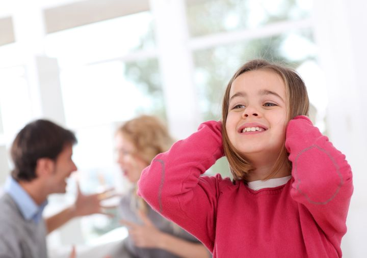 Child hiding her ears from parent's fight