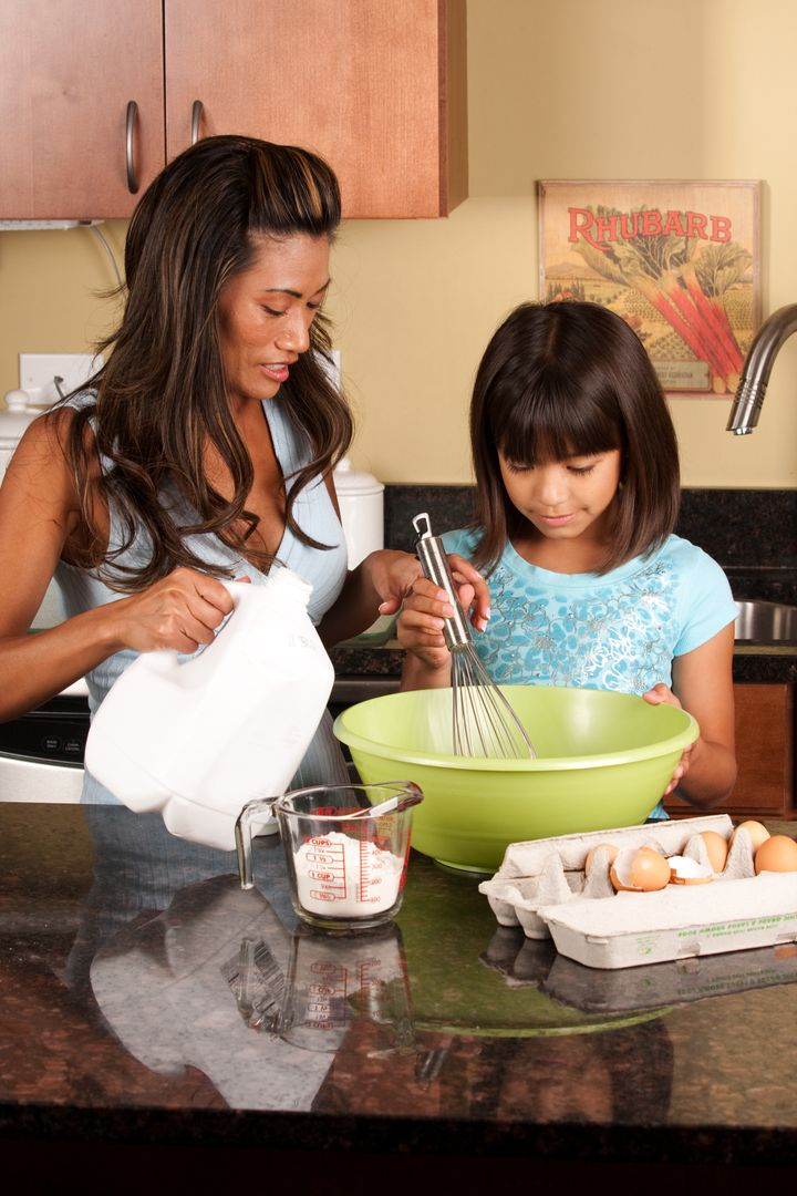 a child helper her mother in the kitchen
