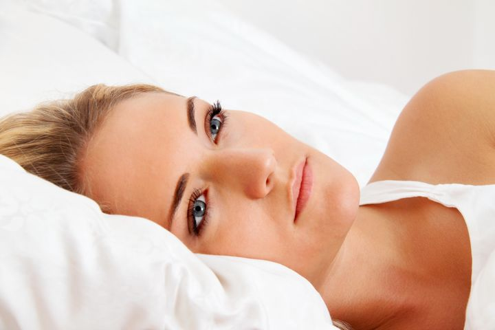 a young woman lies awake in bed....