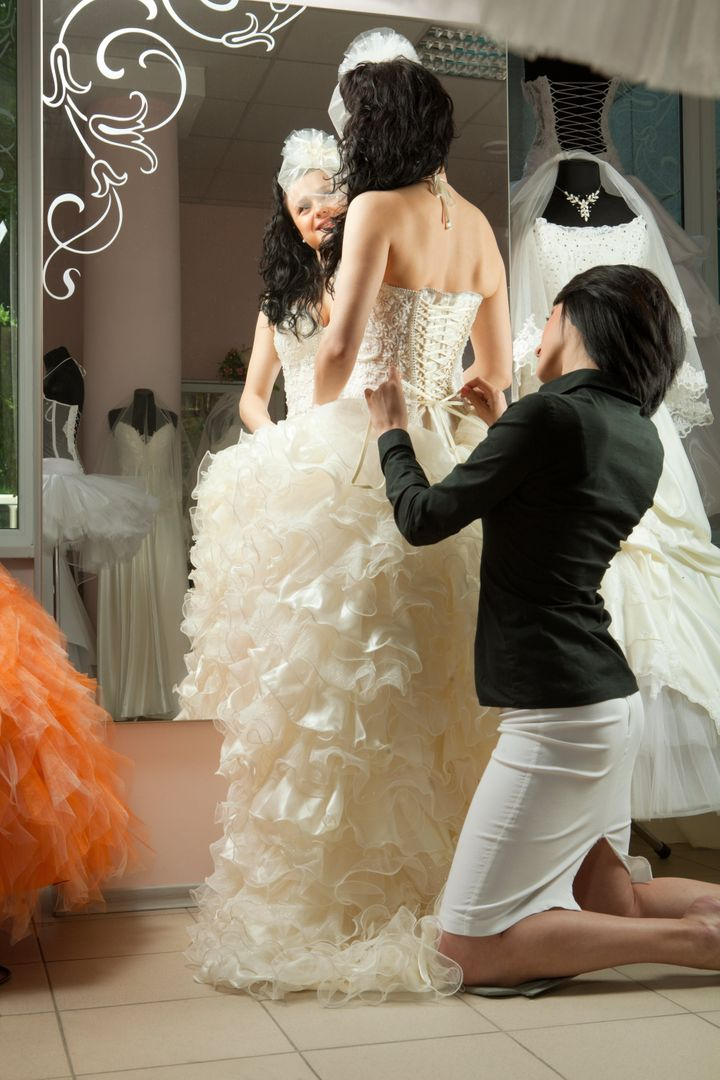 Women making adjustment to wedding gown in professional fashion designer studio