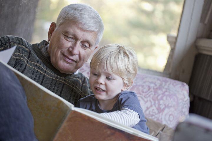 Grandfather reading a book to his grandchild