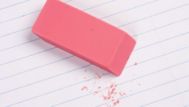 Pink eraser with residue on lined paper.