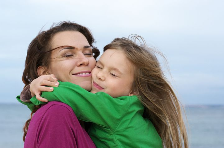 Happy mother and daughter embracing at beach.
