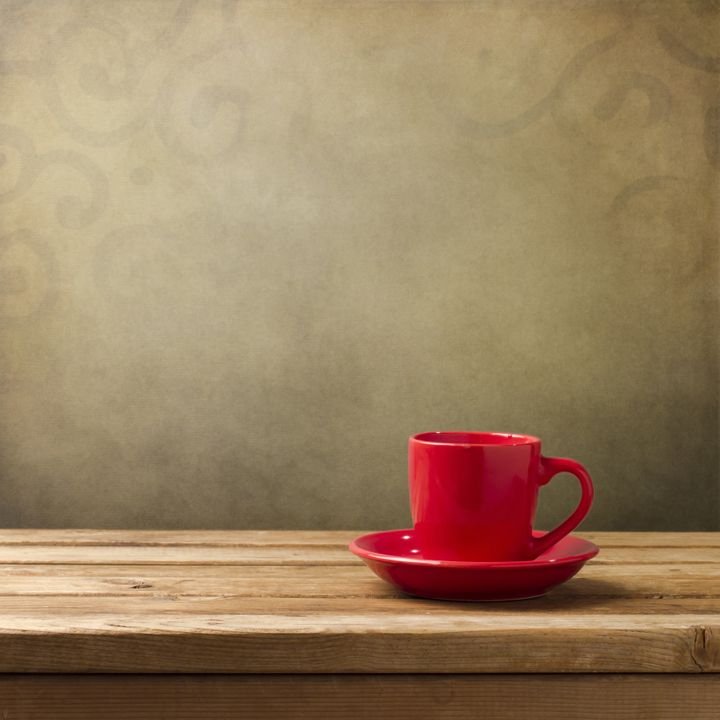 red cup on wooden table over...