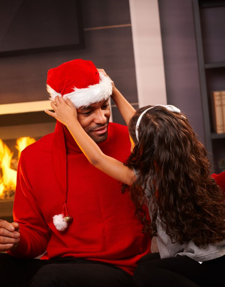 Little girl placing santa hat on father's head at home.