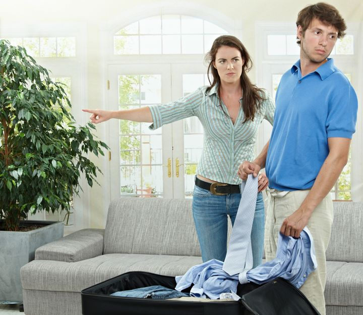 Unhappy couple breaking. Angry woman pointing out, man packing his clothes into suitcase.