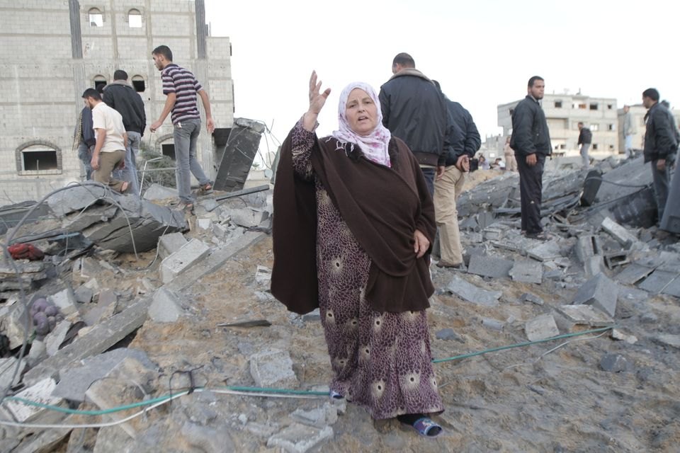 A Palestinian woman shouts anti-Israel slogans on the rubble from her home after the latest Israeli airstrikes in the town of