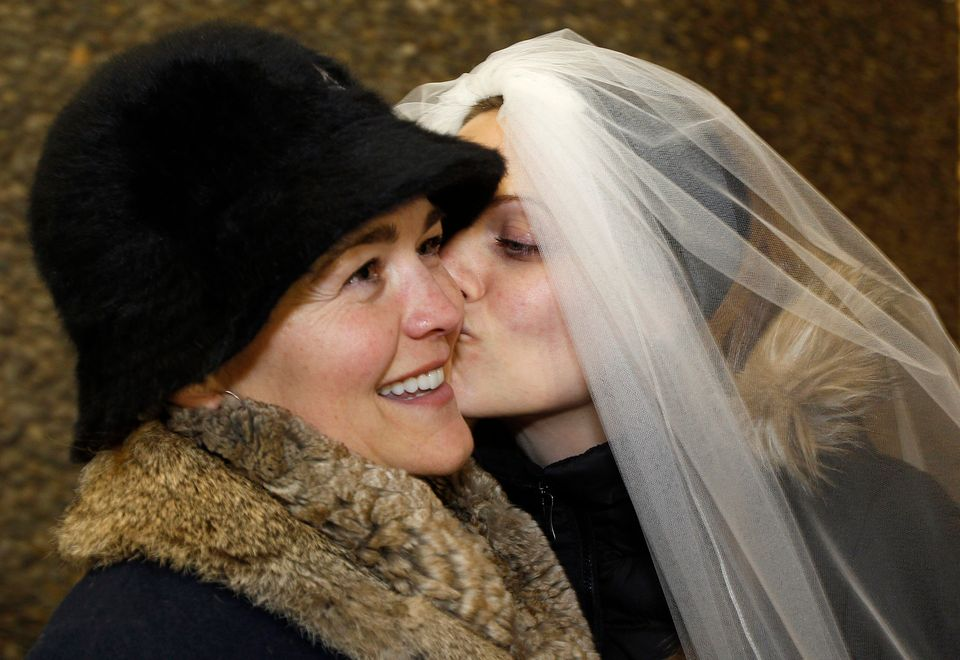Amy Andrews, right, wears a veil while kissing her partner, Jeri Andrews, while waiting to be among the first to be issued a