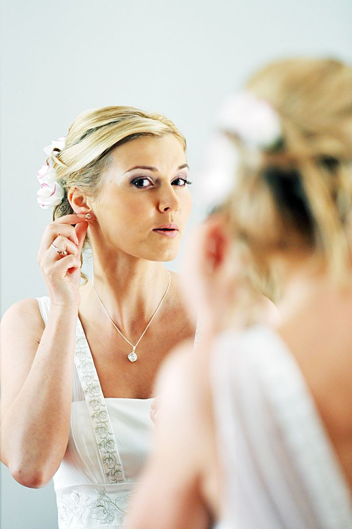 Beautiful bride with wedding gown looking through mirror