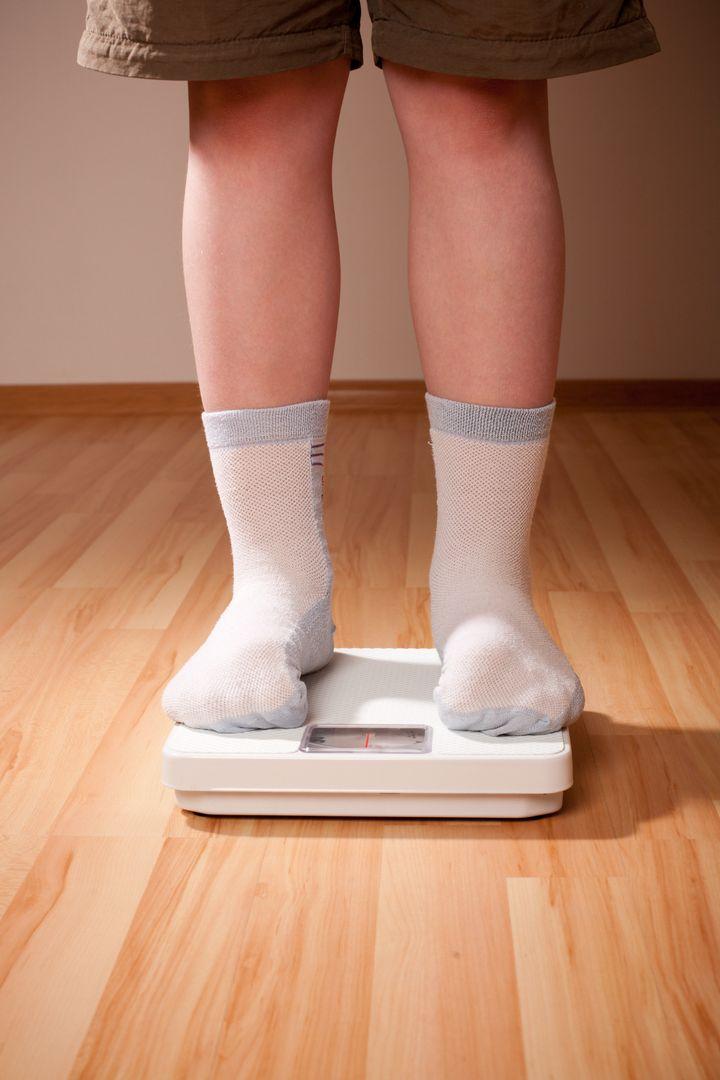 Boy measures weight on floor scales. Legs in shorts and socks standing at floor scales on hardwood floor in living room.