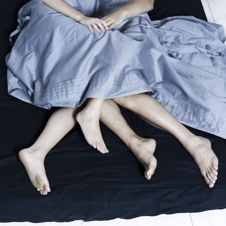 detail close up of loving couple sleeping in bed hand in hands