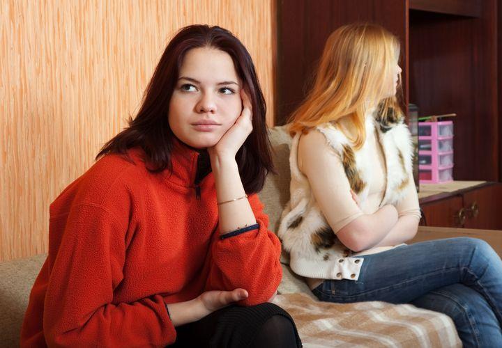 two sad girls having quarrel at ...