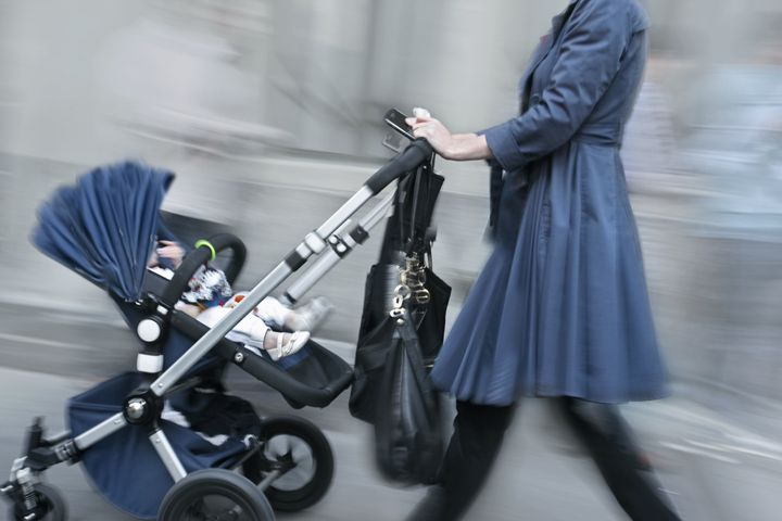 young parent with stroller rushing on the street in intentional motion blur