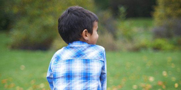 Male toddler in the garden sitting on pumpkin