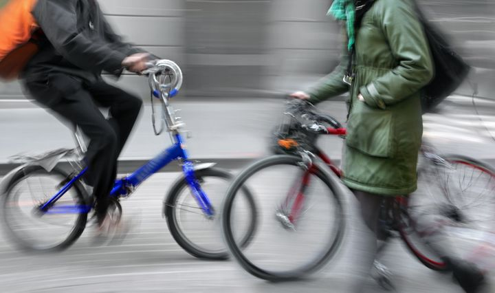 motion blur woman holding bicycle walking on the sidewalk, alternative urban transportation concept, bike rider in the background
