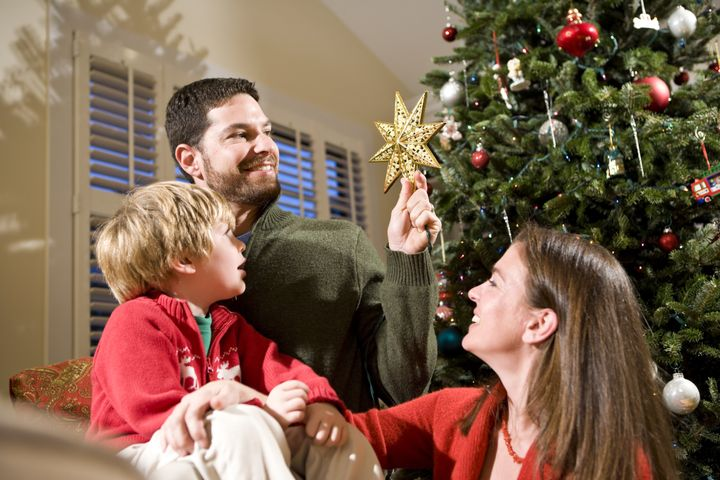 Family with child by Christmas tree, dad holding star