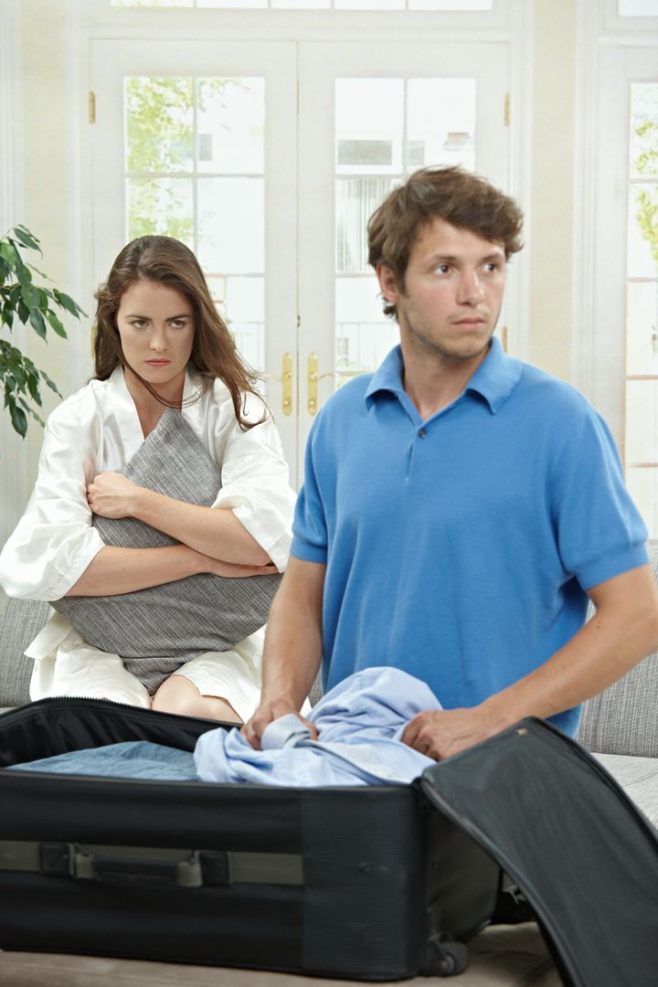 Unhappy couple breaking. Man packing his clothes into suitcase, sad woman hugging pillow in the background. Selective focus on woman.
