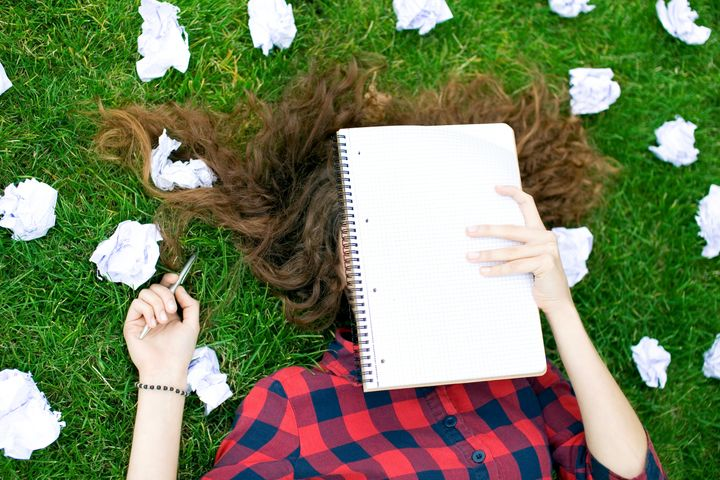 Female Student Surrounded by Crumpled Paper