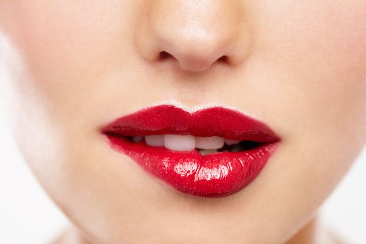 Cropped closeup of a woman wearing red lipstick and biting her lip