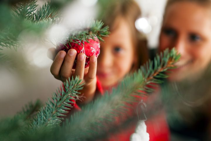 Young girl helping her mother decorating the Christmas tree, holding some Christmas baubles in her hand (Focus on bauble)