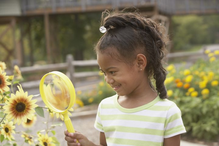 african girl looking at flower...