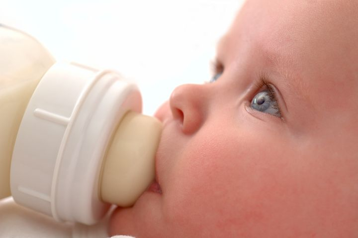 close up of baby drinking his...
