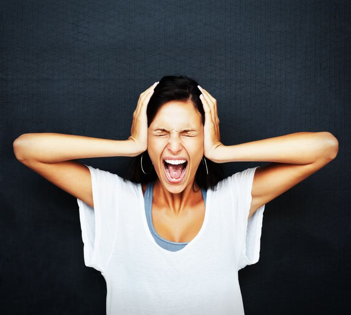 Woman holding head and screaming against blue background