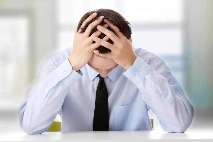 Businessman in depression with hand on forehead