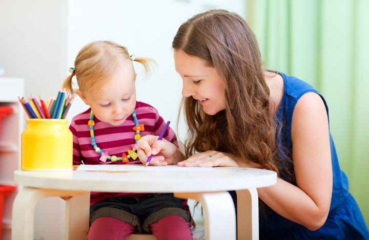 Young mother and her little daughter drawing together