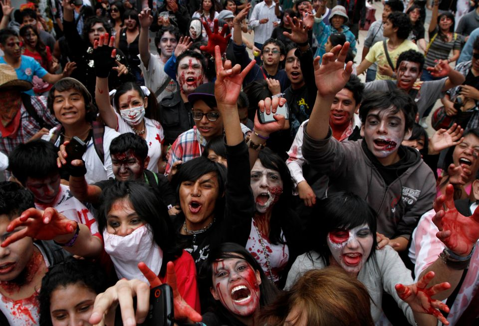 People dressed as zombies react to the camera during a Zombie Walk in the main Zocalo plaza in Mexico City, Saturday, Nov. 3,
