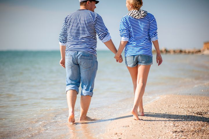 two people walking on the beach