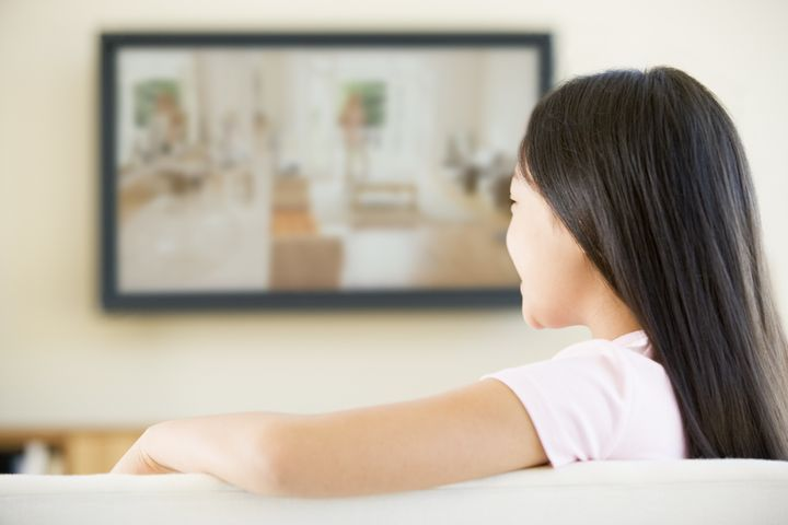 Young girl in living room with flat screen television
