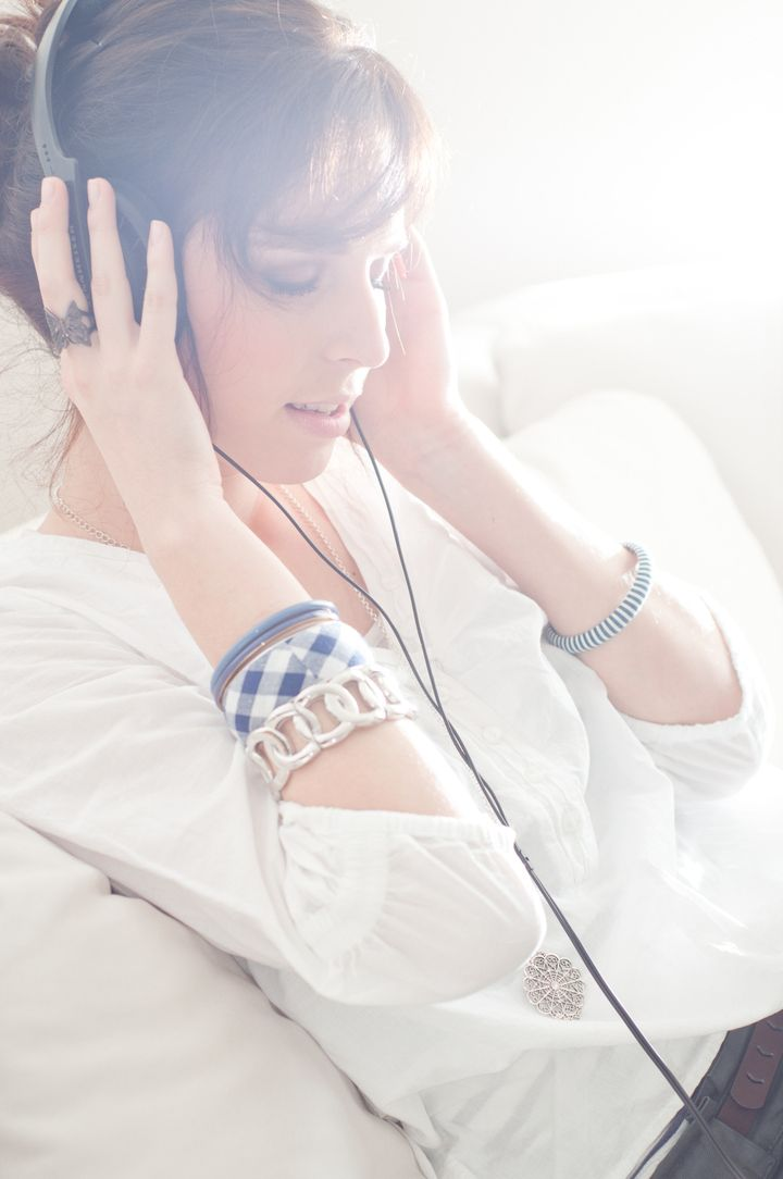 Happy woman with headphones lying down on sofa in lounge, listen to music
