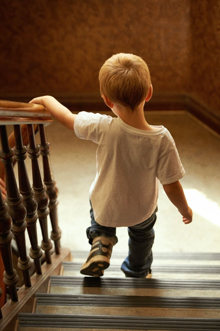 Rear view of a young boy walking down the stairs at home