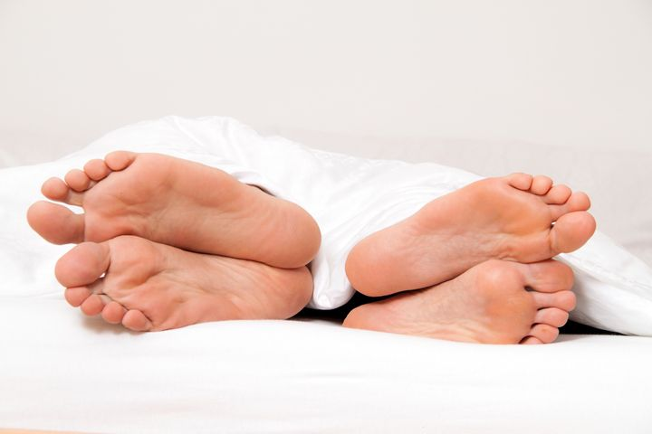 Dier feet of couple in bed. Separation and divorce