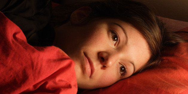 Beautiful female lying in bed trying to fall asleep.  Image for insomnia, sleeplessness, stress, sadness, etc.  Lit by a nigh